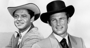 Two men, one wearing a white cowboy hat and the other wearing a black cowboy hat.